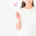 若い女性が✕の表示を持っている