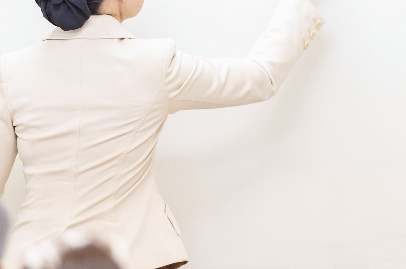 スーツを着た女性のレイキ講師がレクチャーする様子