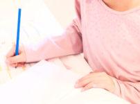 熱心に勉強に取り組むピンク色のシャツの女性