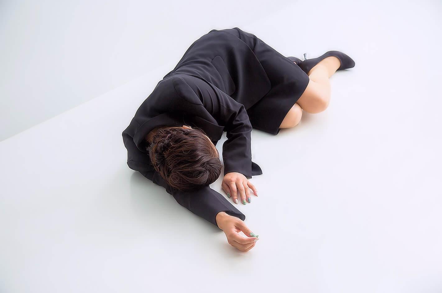 疲労困憊のビジネスウーマンが倒れた様子