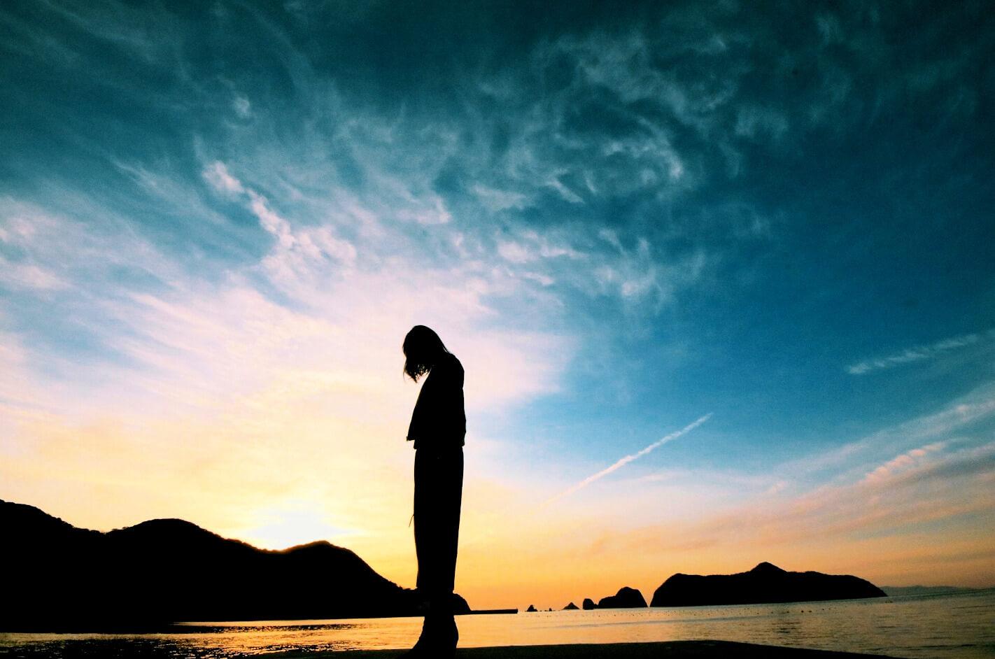 海辺でうつむく女性