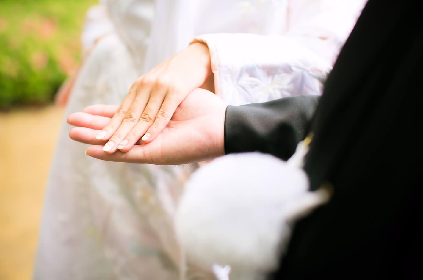 結婚式で手をつなぐ幸せな男女
