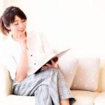 タブレットを見ながら考え事をする清楚な女性