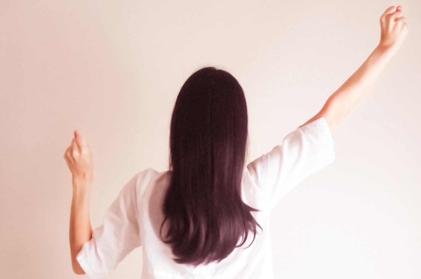 ガッツポーズをする若い女性